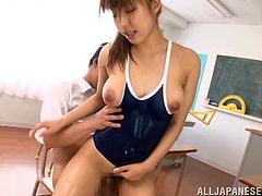 A lewd Japanese chick, wearing a swimsuit, oils her body and lets two guys play with her tits and cunt. After that the men drill the hottie's pussy in the standing position and doggy style.