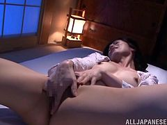 Sexy Asian babe Chisayo Nanami lies in bed wearing the sexiest black thong and toys her little dripping pussy with a small vibrator.