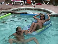 Two kinky nude blondes are having fun in a pool. The girls stroke each other's nude bodies, then rub their pussies against each other.