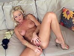 Flamboyant light-haired girl strips on cam demonstrating her big natural boobs and juicy butt. Then she lies on the couch and screws her eager clam with smooth dildo.