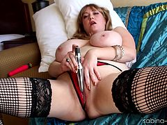 Huge-breasted blonde bitch Sabina Leigh, wearing thong and stockings, is having a good time indoors. She fingers her shaved meaty twat, then massages her clit with a toy.