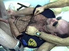 This horny bear cop gets his filthy mouth around some of his prisoners' big hard cocks and enjoys getting his yummy ass fingered.