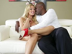 Have a good time watching this long haired blonde, with huge breasts wearing high heels, while she talks dirty sitting on a couch next to an ebony man.
