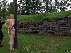 Blonde, pretty and with a very sweet body, miss Delirious is enjoying herself in the backyard and the executor makes sure her experience is one of a kind. After tieing her naked on a wall, the executor walks her to a wooden post where he ties her again and leaves her there to enjoy the rain and some humiliation