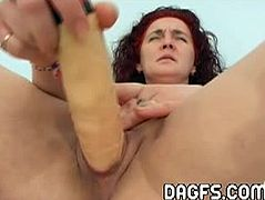 This mature mom with red hair spreads her legs and begins to masturbate. She is using a big vibrator that, in combination with her clit rubbing, takes her to climax.