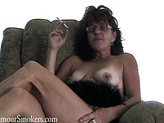 Take a look at this nasty mature amateur woman showing her yummy natural boobs while she sits on the couch and grabs a smoke.