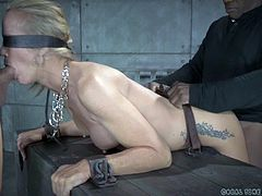 Two sadistic men take turns in fucking a blonde milf from behind. The slutty slave is bending over a wooden cage where another helpless bitch wearing a ball gag is captive. If you are into hardcore sex scenes, dare to click and see a blindfolded Simone sucking dick right down to the balls while being banged.