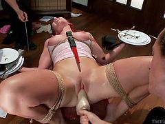 Despite all the distractions, redhead beauty Sophia Locke has a mind blowing orgasm. He legs are bound and she lays back on the coffee table. The redheaded slave must balance plates in each had. But that's not all she also has a dildo in her cunt which makes her moan and cum. She even endures a shock.