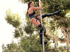 lovely cowgirl with natural tits and in leather outfit plays on the pole in the flexible angles rubs her tits and shows her shaved pussy outdoor
