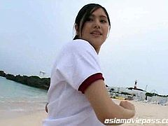 Sweet and innocent looking Asian teen school girl is all wet and getting naughty near the beach.