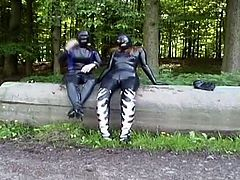 Two stunning girls in latex outfits are outdoors pleasuring each other
