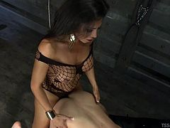 The slave has to suck her lady dick. This sexy shemale is dressed in a fishnet stocking bodysuit. Jaquelin makes her man climb on top of her and ride her stiff cock, as she tugs on Lucas pathetic pecker. Watch, as she takes him really hard from behind. His asshole is being stretched out by her huge dick.