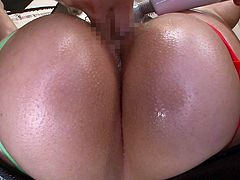 Her giant tits are hanging out of the side of her bathing suit, and she is covered in oil all over. She is fingered and has a vibrator, used on her cunt. She grabs each guy's cock and works them with her hands, before sitting on one guy's face, and sucking the other off.