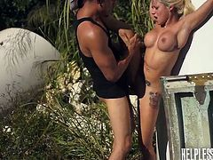 Marsha's tits, blonde hair and crazy body can drive a man really mad of passion over her. The slut is insanely fucked, while her hands are in shackles in a remote place outdoor. Then, she's taken elsewhere, mouth gagged and awfully banged. Click to watch the busty teen sucking cock, while blindfolded! Enjoy.