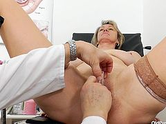 This old slut is at the doctor's office, to get a check up of her vagina. She has her legs spread nice and wide in the stirrups and the gyno, checks out her genitals. Everything is looking good, as he fingers her deep.