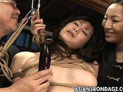 Poor Asian lady is captured and tied up to the ceiling. As she is unable to move, a kinky couple starts playing with her dirty hairy pussy and making her cum with various toys and items.