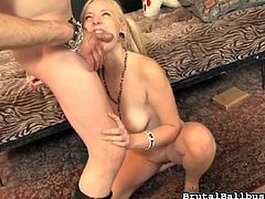 The cute skinny blonde has tied a leather strap around his cock and balls, to keep his cock nice and hard. She sucks him off and bites down on his penis. She also bites down on his swollen ball sack. What a mean bitch!