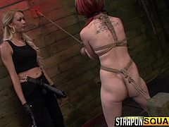 The mistresses have big black strapons on and they have no problem, using their big fake black cocks on this little redheaded slave. They have the slave tied up with rope in the sex dungeon and they whip her really hard.