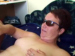 This short-haired mature is laying in bed, wearing a pair of stockings. She is blowing cock while the guy's whose cock she's blowing rubs her mature fanny.