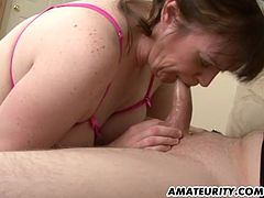 A busty amateur Milf sucking and fucking a young dick on a sofa ! Homemade hardcore action with this hot housewife with cumshot on her big tits !