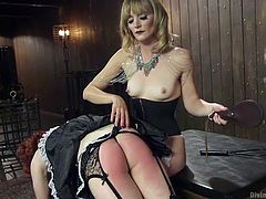 This crossdressing slut needs to be punished and the lovely mistress is going to teach him a lesson with a paddle. The redhead beta male maid is over her knee, and his ass is getting so red from the beating, she gives him. Now she has a strap on surprise for him.