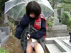 This Japanese schoolgirl has a toy in her panties. She walks through a cemetery and flashes her panties and the vibrator that stimulates her pussy while holding an umbrella.
