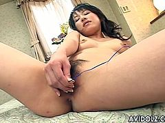 Slim smiling Japanese girlie in yellow bikini teases hairy cunt with toy