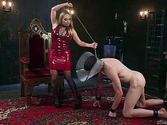 Sexy Aiden transformed into a tough woman, a real mistress, who knows how to deal with an obedient slave. The horny blonde milf is wearing a kinky red latex molded dress, which seems to suit her perfectly. The naked guy's legs and hands are in chains and he has to crawl on the floor, following this bitch.