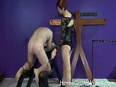 Leather-clad dominatrix with short red hair pegging her sex slave