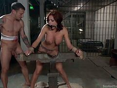Britney Amber is wearing a kinky ball gag and her hands have been tied with ropes. The horny guy makes his appearance and seems eager to take off her sexy bra and bikini. See him fucking the slutty redhead babe from behind!