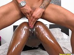 This nasty slut is on her back and getting fucked like crazy. He whole body is oiled up, what makes her beautiful black skin nice and shiny. The ebony slut moans loudly, as her man's white cock slides in and out of her vagina.