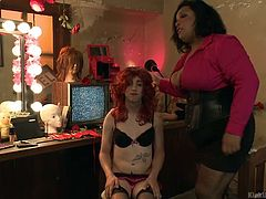 This wimpy man is dominated by his chubby black mistress in the most humiliating way possible. The black goddess makes him dress up like a woman. He has to wear a red wig, lingerie and make up, while strutting around like a slut.