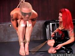 Tattooed redhead with a nice body torturing a stranger