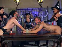 It's a good thing that you aren't either of these two guys right now, unless you're into being dominated by cruel mistresses. They torture these guys mercilessly, laughing the whole time they're doing it. The blonde, brunette and redhead bend the guys over the table and ass-fuck them with strap-ons.