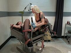 Lorelei has control over Phoenix, who is strapped to the exam table, helpless but to take what is done to her. Electrodes are attached all over her, and she is shocked as well as stimulated in her nipples, pelvic area, and pussy. Phoenix endures fingers, vibrators, nipple clamps, gags and bonds.