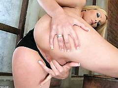 Blonde Sophie Moone plays with her moist beaver after posing naked