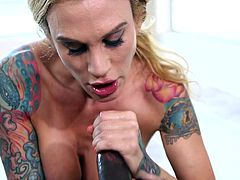 A sexy blonde milf with colorful tattoos adjusts her bra, as to reveal her fascinating big tits. Click to watch bitchy Sarah, crawling on the floor and sucking a big black cock, on knees. Enjoy the spicy moments!