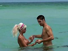 Delta White is a busty blonde that is on the beach with her boyfriend. He is putting on some sun screen on her tits and on her pussy so she does not get burnt.