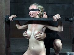 Jeanie heeds her executor's commands, although she cannot see him and she's cinched tight in the device, he has prepared for her. The blindfolded submissive straddles another part of the device, directly in contact with her pussy. What else is in store for this pretty blonde?