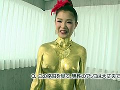 Check out this Asian girl completely painted gold. She dazzles us with her body and cute smile. The hottie winks at the camera and timidly kneels in front of her man's penis to suck him off. The gold queen works the shaft, while using her lips on the head.