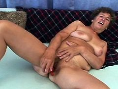 Ludmila, a mature slut with wrinkled face and saggy boobs, still has a voracious hunger for hard cocks She is fucking her hairy old cunt with a red dildo and then, happily takes Steve's dick in her mouth.