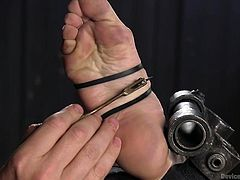 The master controls this slave and makes her do what he wants. She is locked in the bondage contraption, with her legs spread wide. The machine fucks her cunt and the master teases her soles. She yells in pain, as the pressure on her feet becomes more intense.