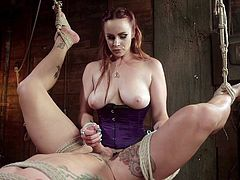 A busty mistress with red hair, wearing kinky stockings, has strongly bonded a naked guy with ropes. The dominant bitch can't wait to unleash her fantasies and fuck this tattooed man with a strap on. Her slave enjoys a hand job and his punishement is whipping...