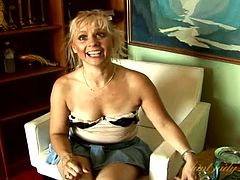 Mature in a miniskirt gives an interview and flashes