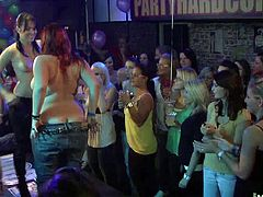Youll see several bashful ladies get up there and begin pealing off their clothes, only to hide their boobs and pussy but, one big redhead takes off everything and gets ready for the party to crank up.