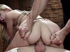 Juggy blond babe Alina West is tied up and suspended in the dark BDSM room